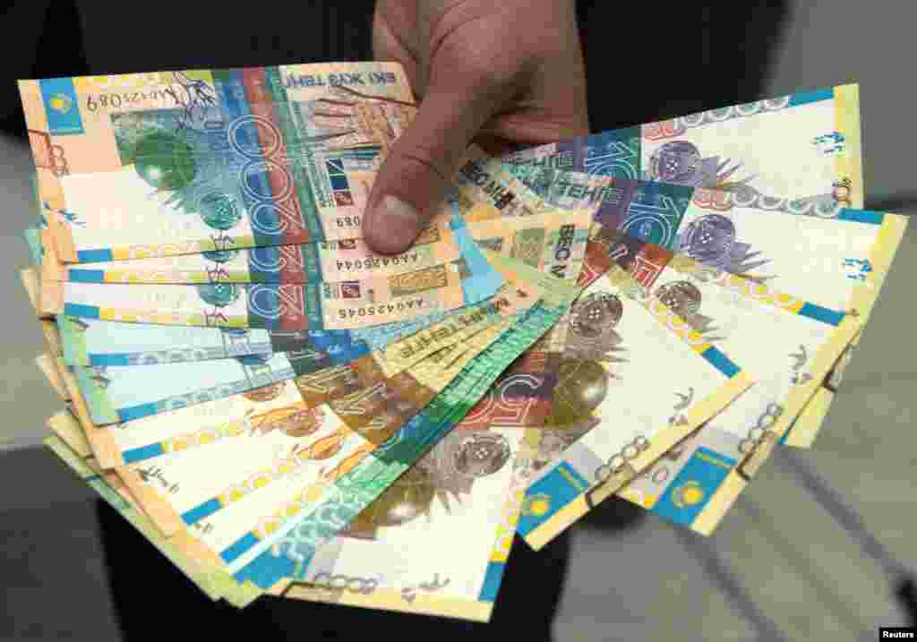 A Kazakh National Bank employee shows a set of Kazakhstan's new tenge banknotes during a presentation in Almaty in 2006.