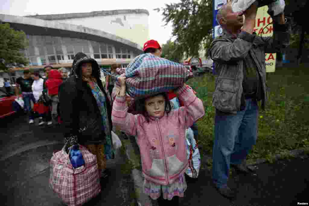 Residents of the Donetsk region in eastern Ukraine prepare to board buses for Rostov-on-Don in Russia from a collection point in the city of Donetsk on July 14. (Reuters/Maksim Zmeyev)