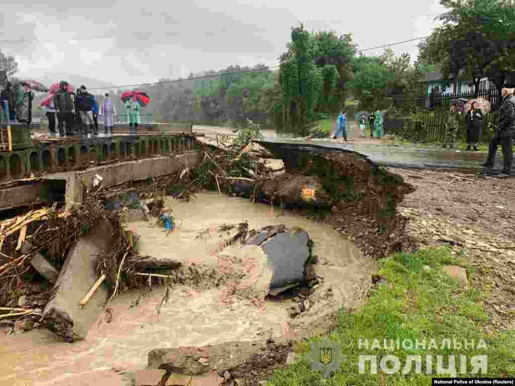Місцеві жителі стоять на узбіччі зруйнованої потоками води дороги. Івано-Франківська область, 23 червня