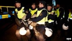 Швед полициячылары Мальмө шаарынын качкындар борборундагы мигрантты алып баратат.