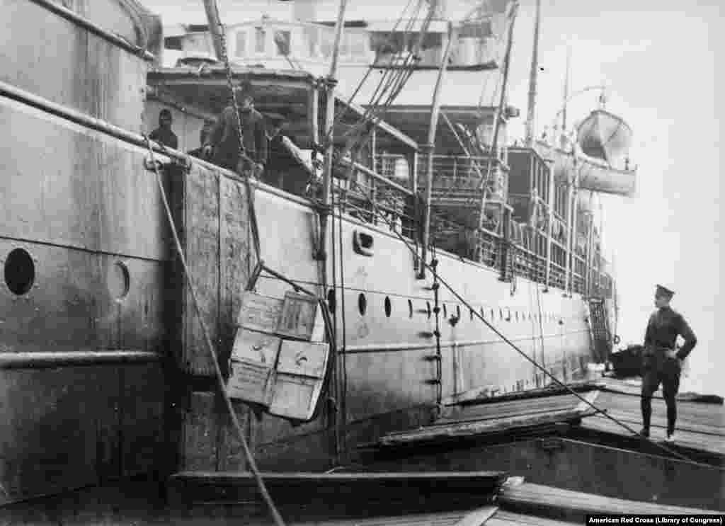 """""""Američka hrana za Ruse"""" koja se ukrcava na brod u Hamburgu. Kada je 50.000 kartona kondenzovanog mleka otpremljeno u Rusiju, nedugo nakon revolucije 1917. godine, na njima je pisalo """"Od slobodne Amerike za slobodnu Rusiju""""."""