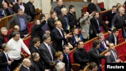 Ukrainian opposition deputies react during a session in parliament in Kyiv on January 29 in which the amnesty law was passed, without their participation.