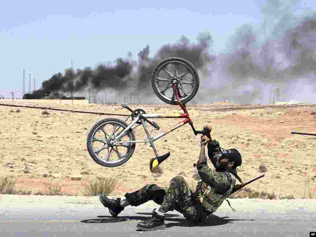 A Libyan rebel with a bicycle celebrates the liberation of Al-Qawalish, 100 kilometers southwest of Tripoli, after six hours of battle. In the background smoke rises from a power station that was shelled by retreating soldiers loyal to Muammar Qaddafi.Photo by Gaia Anderson for The AP
