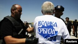 "Police detain a Serb wearing a T-shirt reading ""Greater Serbia"" during a celebration of the anniversary of the 1389 Battle of Kosovo Polje at Gazimestan on June 28."