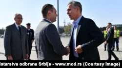 NATO Secretary-General Jens Stoltenberg (right) is greeted by Serbian Defense Minister Aleksandar Vulin in Belgrade on October 6.