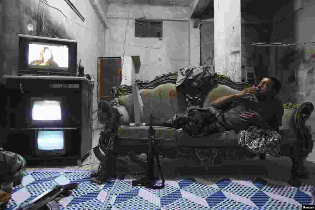 A Free Syrian Army fighter rests on a sofa as he watches television and surveillance monitors inside a room in Aleppo's Karm al-Jabal district. (Reuters/Muzaffar Salman)