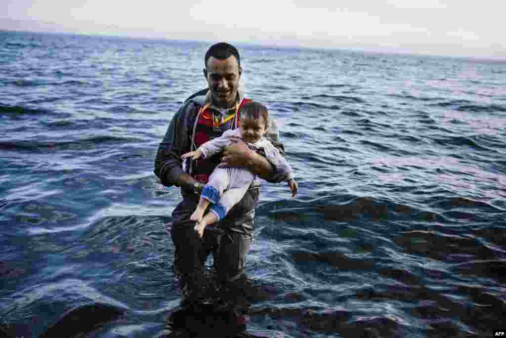 A man carries his child shortly after arriving with other refugees and migrants on the Greek island of Lesbos, after crossing the Aegean Sea from Turkey. (AFP/Dimitar Dilkoff)