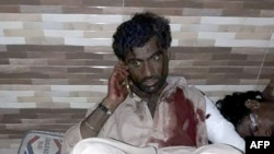 An injured blast victim talks on a mobile phone at a local hospital following the bomb attack.