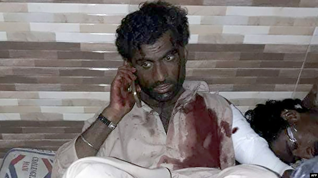 An injured Pakistani blast victim talks on a mobile phone at a local hospital after a bomb explosion at the shrine of 13th century Muslim Sufi saint Lal Shahbaz Qalandar in Pakistan on February 16.