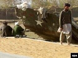 Мужчины-афганцы сушат рис у разбитого бронетранспортера , 15 ноября 2001 года. Иллюстративное фото.
