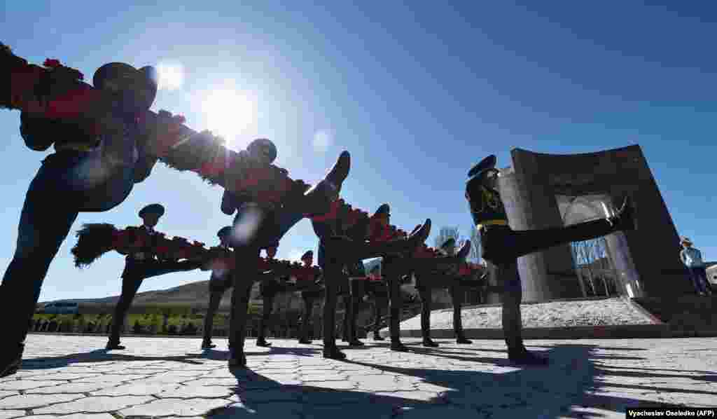 Kyrgyz national honor guards lay a wreath at a monument to those killed during the April 2010 uprising at the Ata-Beyit cemetery outside the capital, Bishkek, on April 7. (AFP/Vyacheslav Oseledko)