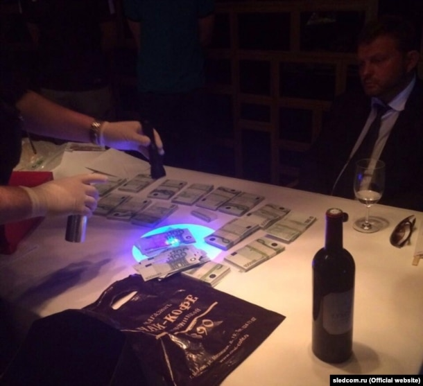 The Investigative Committee shared photographs of Nikita Belykh at a restaurant as investigators shined ultraviolet flashlights at an alleged bribe of 400,000 euros.