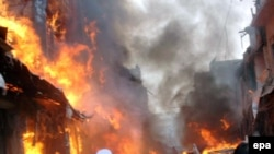 Flames rise from the scene of a powerful bomb blast at a Peshawar market.