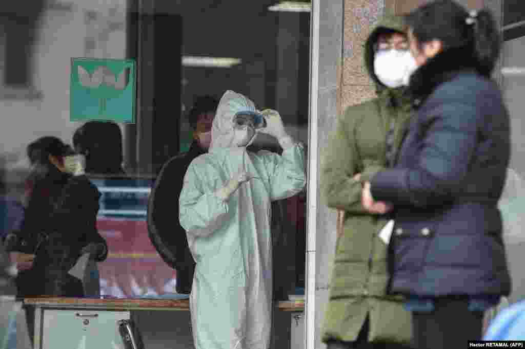 A nurse (center), wearing protective clothing to help stop the spread of a deadly virus which began in the city, looks at a thermometer at the Wuhan Fifth Hospital in Wuhan on January 24, 2020.