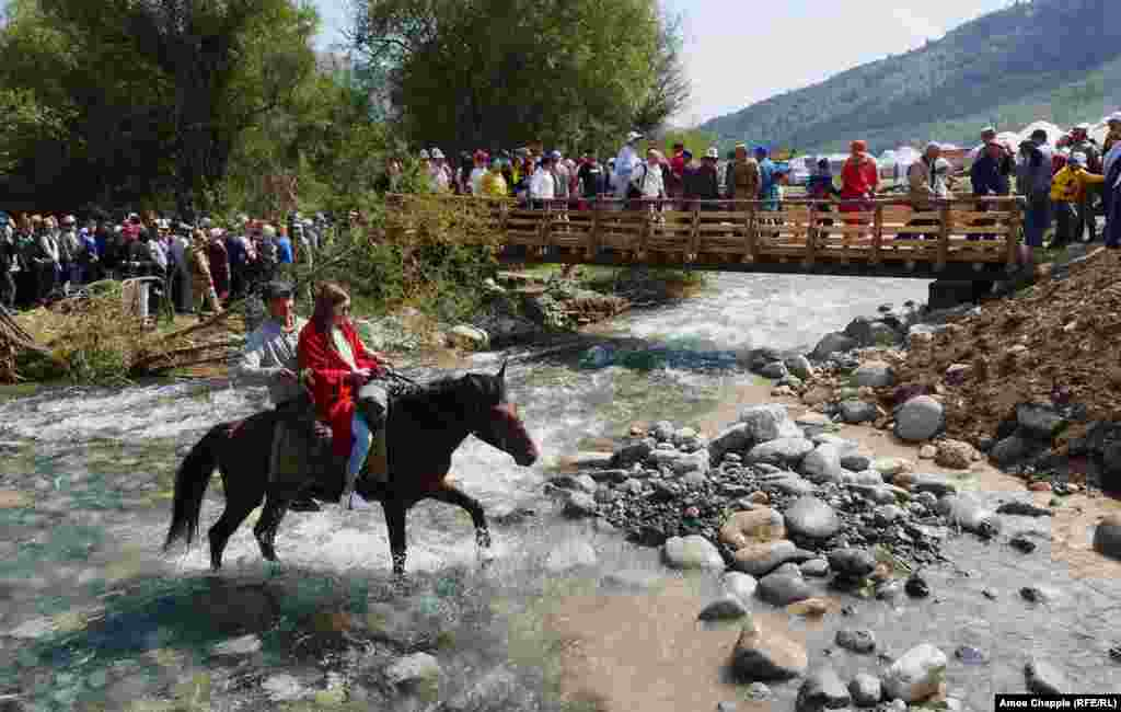 Young locals take the low road as their horse clatters through a mountain stream on the way to the opening ceremony at Kyrchyn Gorge.