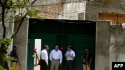 "Pakistani security officials gather outside the former hideout of Al-Qaeda leader Osama bin Laden on May 4. The intelligence service called the failure to find bin Laden there ""an embarrassment."""