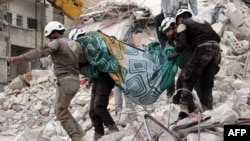 Syrian humanitarian volunteers, known as the White Helmets, carry a body retrieved from the rubble following a reported government airstrike on the town of Ariha, one of the locations mentioned in Amnesty's report. (file photo)