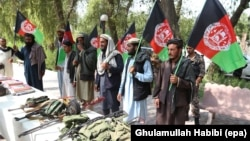 FILE: Former Taliban members hold national flags as they surrender their weapons during a reconciliation ceremony in in the eastern city of Jalalabad in August.