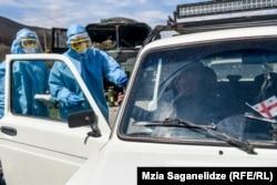 Forțe de securitate georgiene verifică mașinile și persoane care merg spre Tbilisi, pe 31 martie, când carantina totală a intrat în vigoare. (Mzia Saganelidze, RFE/RL)