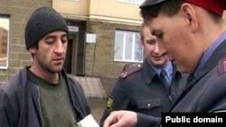 Полицейский в России проверяет документы трудовых мигрантов из Таджикистана.