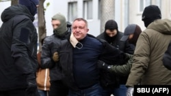 Ukrainian Security Service officers detain Major General Valeriy Shaytanov on suspicion of high treason and terrorism in Kyiv on April 14.