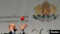 Румен Радев ловит яблоко, брошенное ему журналистом в качестве подарка на пресс-конференции, София, 2016 год