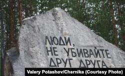 """Сталиндік террор құрбандарына Сандармох зиратында Юрий Дмитриевтің бастамасымен қойылған ескерткіш тастағы """"Адамдар, бір-біріңді өлтірмеңдер!"""" деген жазу."""