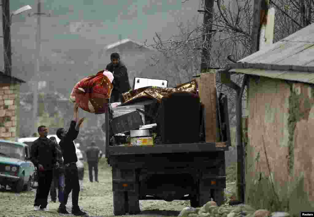 Local residents carry their belongings as they flee from the Nagorno-Karabakh village of Talish on April 6. (Reuters)