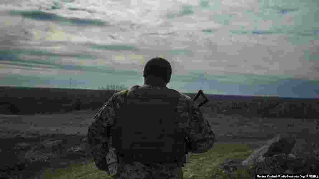 Солдат 30-ої окремої механізованої бригади йде у напрямку українських позицій. На горизонті – підтримувані Росією сепаратисти