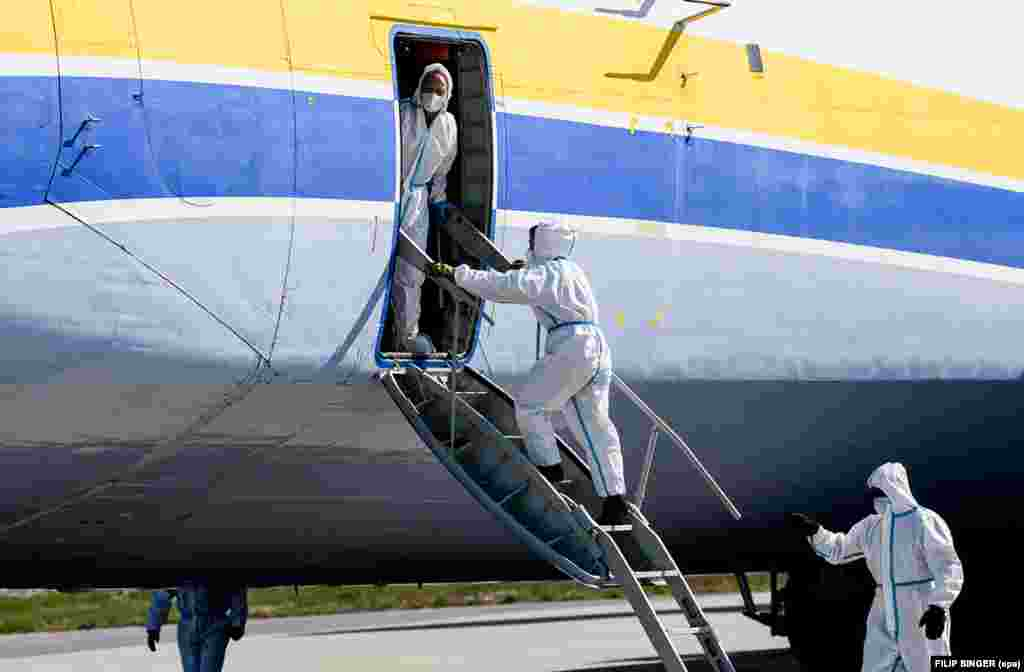 The crew of the Antonov wearing protective equipment after landing in Leipzig on April 27