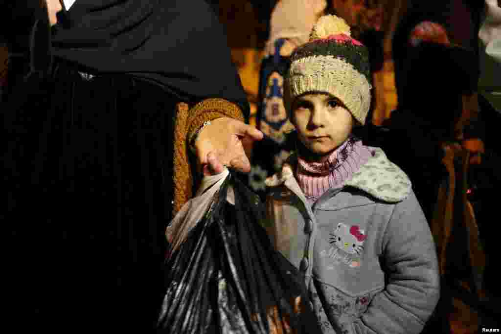 A Syrian girl waits with her family, who say they have received permission from the Syrian government to leave the besieged town, after an aid convoy finally entered Madaya, Syria, on January 11. Thousands have been trapped without supplies for months and people are reported to have died of starvation. (Reuters/Omar Sanadiki)
