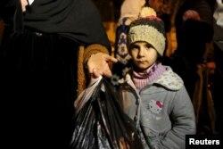 دختر سوری در مضایا همراه مادرش منتظر هستند تا اجازه خروج از شهر به آنها داده شود