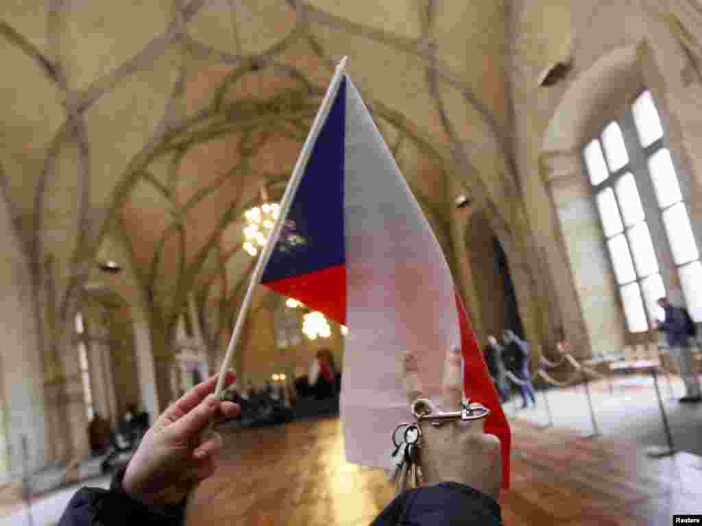 "A man waves a Czech flag and a set of keys in homage to Vaclav Havel inside Prague Castle. The jingling of keys, symbolizing the ""unlocking of doors,"" was a major component of mass demonstrations led by Havel on Wenceslas Square in 1989."
