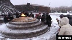 Активисты читают молитву после возложения цветов к монументу «Отан Ана» в память о жертвах Декабрьских событий 1986 года. Астана, 17 декабря 2015 года.