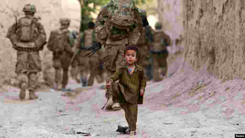 An Afghan boy plays on a street as U.S. Army soldiers patrol during a mission in the Zahri district of Kandahar Province on May 30.  (Reuters/Shamil Zhumatov)