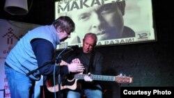 Юры Несьцярэнка дапамагае Андрэю Макарэвічу наладзіць гітару на канцэрце