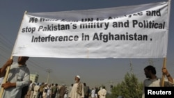 Men hold a banner aloft during a demonstration in Kabul against crossborder shelling attacks on August 30.