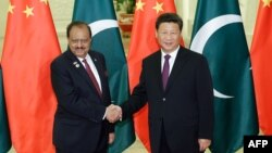 Chinese President Xi Jinping, right, shakes hands with Pakistani President Mamnoon Hussain before their meeting at the Great Hall of the People in Beijing on September 2.