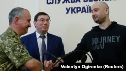 Russian journalist Arkady Babchenko (right) shakes hands with Ukrainian Security Service chief Vasyl Hrytsak (left) as Prosecutor-General Yuriy Lutsenko looks on at a news briefing in Kyiv on May 30.