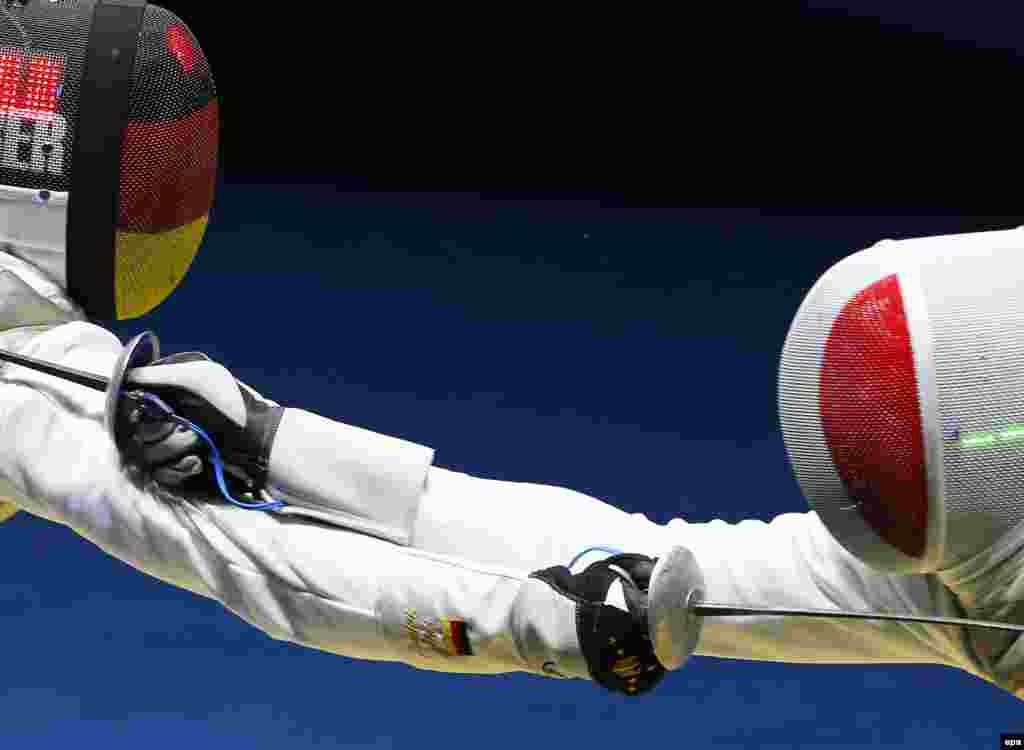 Peter Joppich (left) of Germany in action against Enzo Lefort of France during the men's individual foil fencing event.