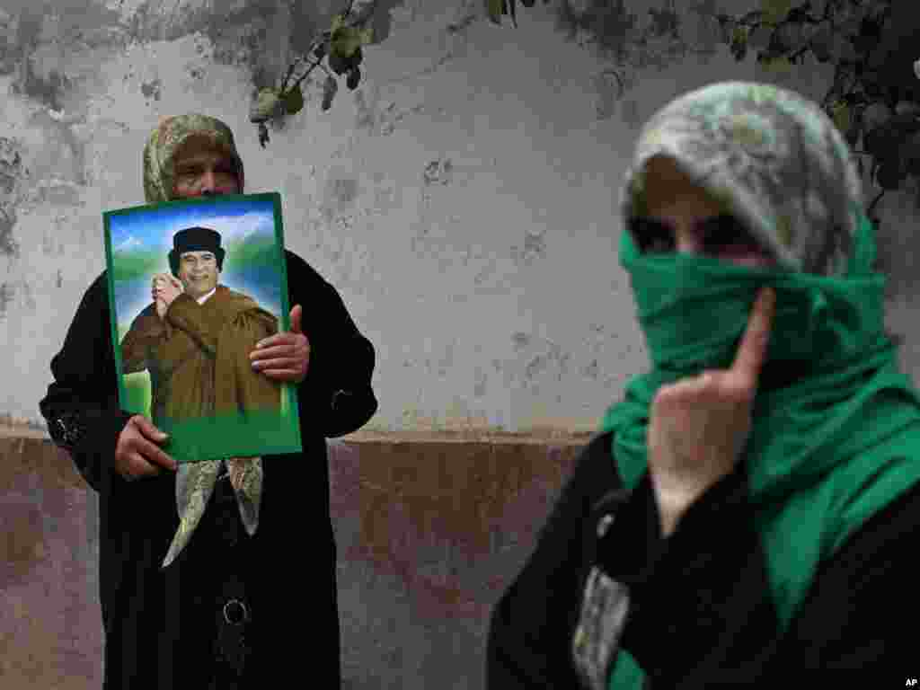 A woman holds up an image of Libyan leader Muammar Qaddafi during a protest in front of the Hungarian Embassy in Tripoli, Libya, on August 11. Dozens of reported residents of the town of Majar, where the Libyan government claims that 85 civilians were killed in a NATO air strike on August 9, protested in front of the embassy, which is currently representing the U.S. and the EU interests in Libya. Photo by Dario Lopez-Mills for AP