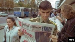 A military cadet pauses to read newspaper coverage of the presidential election at a kiosk in downtown Minsk.