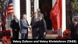 Генералният секретар на комунистическата партия на СССР Михаил Горбачов се ръкува с вицепрезидента на САЩ Джордж Буш. До тях е президентът Роналд Рейгън. Снимката е направена преди началото на среща в Ню Йорк през декември 1988 г.