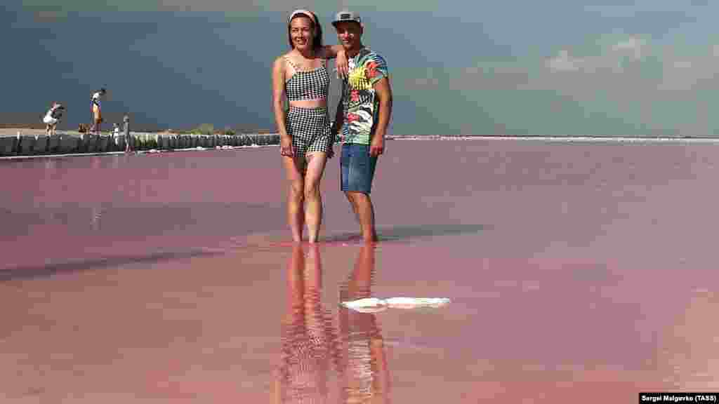 Відпочиваючі фотографуються на тлі рожевого озера