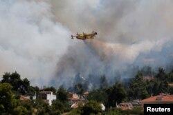 Un avion de stingere a incendiilor se îndreaptă spre combaterea acestora de lângă satul Rodopoli, la nord de Atena, Grecia, 27 iulie 2021.