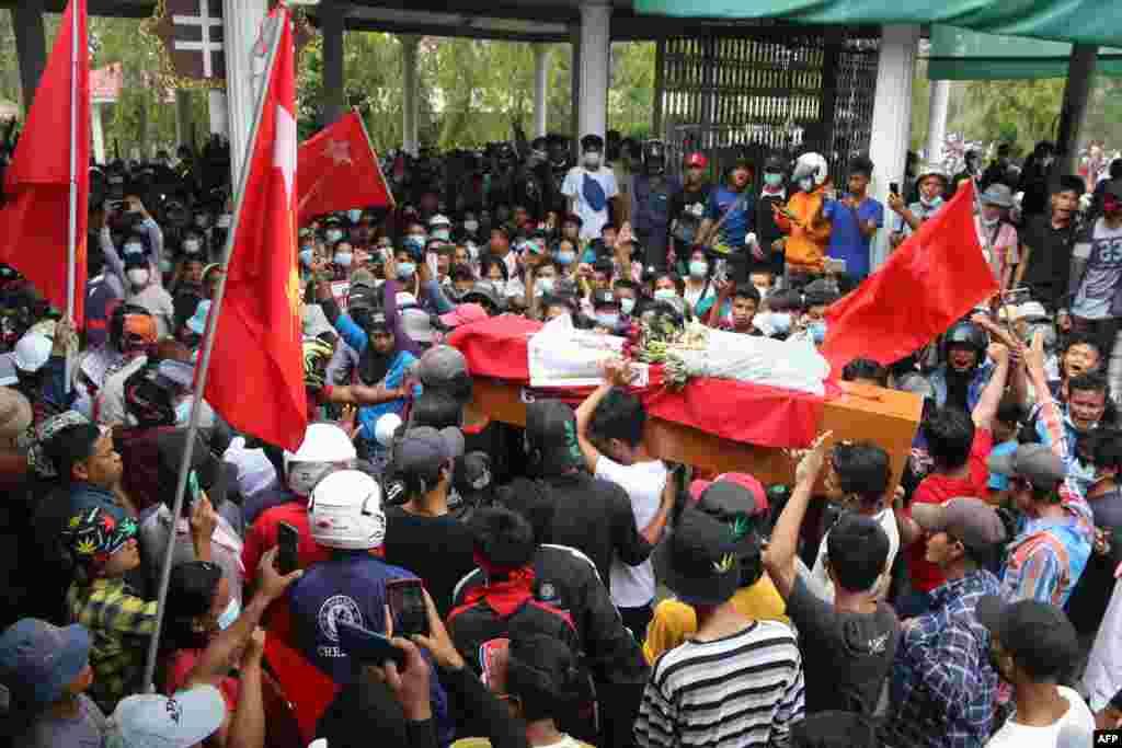 Церемония прощания с погибшим участником протестов. Люди несут гроб на руках и салютуют в знак уважения поднятыми вверх тремя пальцами – жест символизирует сопротивление военному перевороту