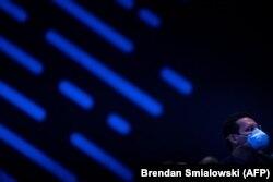 Чоловік у масці проти коронавірусу слухає виступ Ілона Маска на конференції Satellite 2020. Вашингтон, США. 9 березня 2020 року