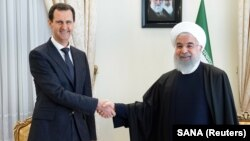 Syrian President Bashar al-Assad (left) shakes hands with Iranian President Hassan Rohani in Tehran in February 2019