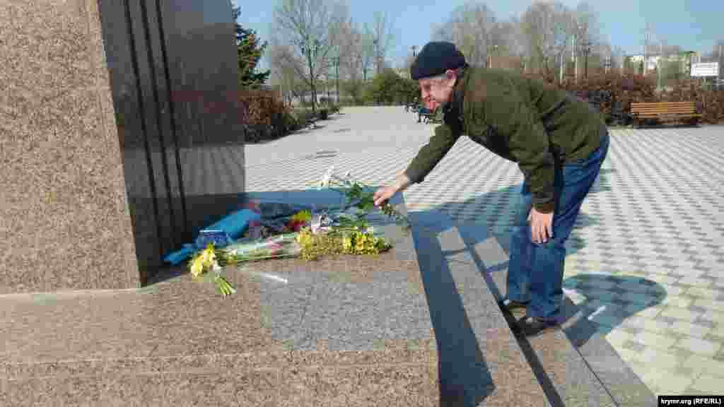 Мужчина возлагает цветы к памятнику Тарасу Шевченко, Севастополь