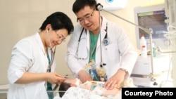 Кардиохирург Кайрат Куатбеков (справа) вместе с коллегой проверяют здоровье ребенка.